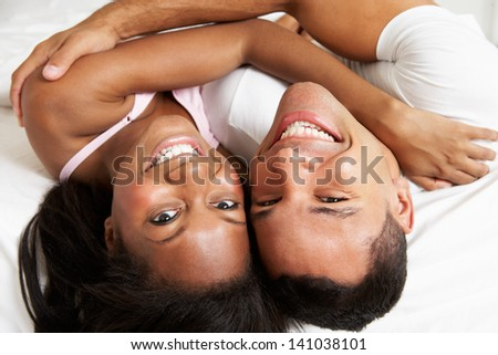 Couple Relaxing In Bed Wearing Pajamas - stock photo