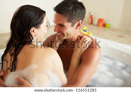 Couple Relaxing In Bubble Filled Bath