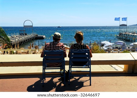 Couple relaxing in chairs on Croisette promenade in Cannes, France - stock photo