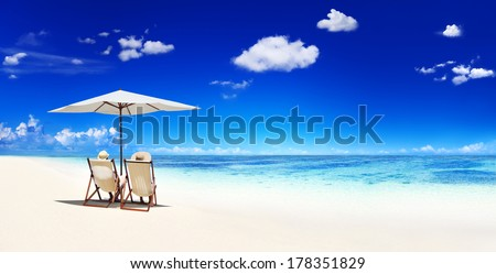 Couple Relaxing in Deck Chairs at Beach