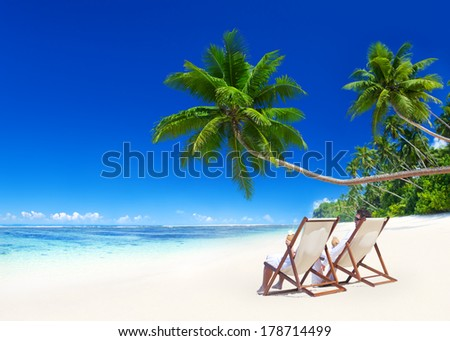 Couple Relaxing in Deck Chairs on Tropical Beach - stock photo