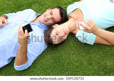 Couple relaxing in grass while using smartphone - stock photo
