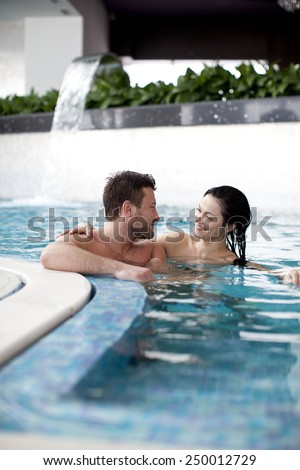 Couple relaxing in jacuzzi of spa center  - stock photo
