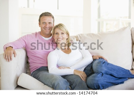 Couple relaxing in living room and smiling - stock photo