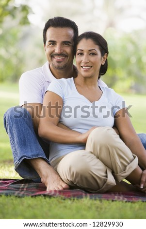 Couple relaxing in park sitting on blanket - stock photo