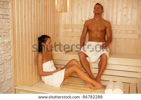 Couple relaxing in sauna with eyes closed.?
