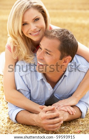 Couple Relaxing In Summer Harvested Field - stock photo