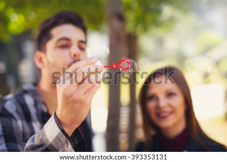 Couple relaxing in the park with bubble blower. Selective focus - stock photo
