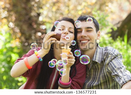 Couple Relaxing in the Park with bubble blower. Spring time - stock photo