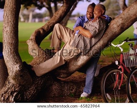 Couple relaxing in tree - stock photo