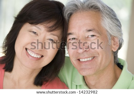 Couple relaxing indoors and smiling - stock photo