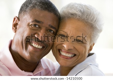 Couple relaxing indoors kissing and smiling - stock photo