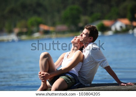 Couple relaxing on a lake bridge in summertime - stock photo