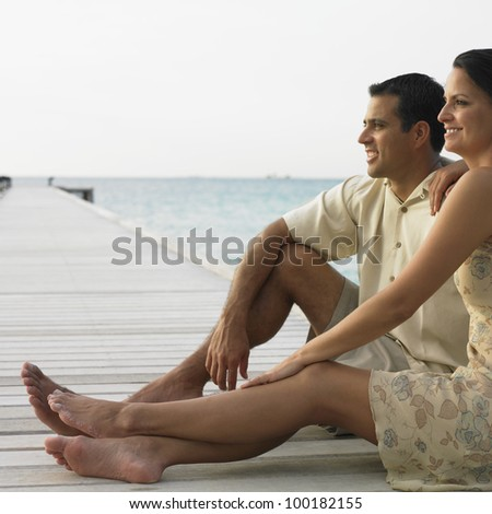 Couple relaxing on a pier - stock photo