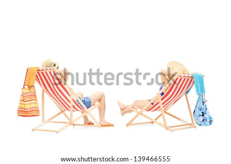 Couple relaxing on a sun loungers, isolated on white background - stock photo