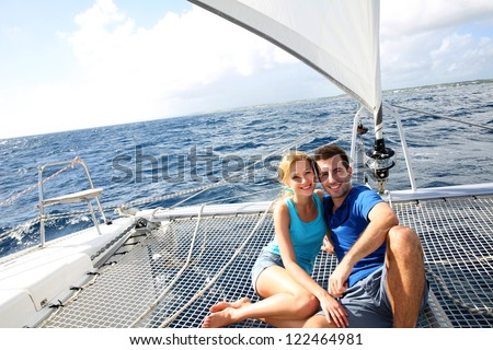 Couple relaxing on catamaran net looking at the sea - stock photo