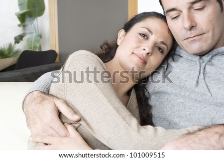 Couple relaxing on sofa at home, holding each other. - stock photo