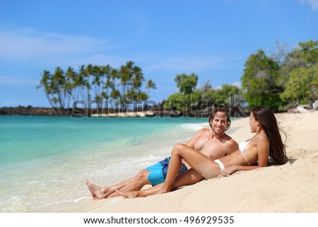 Couple relaxing on suntan beach vacation relaxation holiday. Happy young adults sunbathing together tanning under the tropical sun travel destination. Friends talking enjoying their holidays.