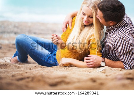 Couple relaxing on the autumn beach - stock photo