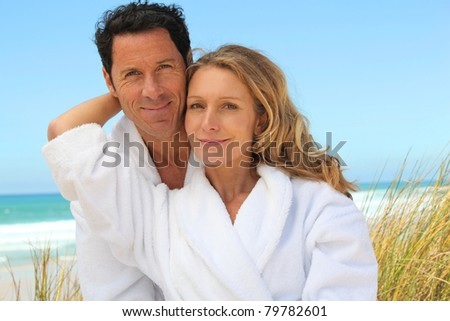 Couple relaxing on the beach in toweling robes - stock photo