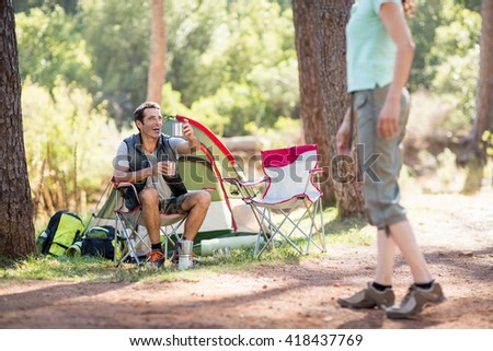 Couple relaxing on their camp site on the wood - stock photo