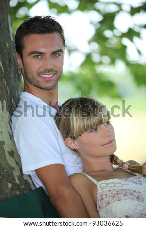 couple relaxing under a tree