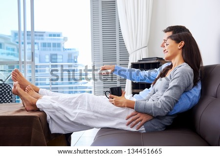 couple relaxing watching tv at home on the couch with embrace and cuddle - stock photo