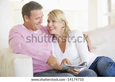 Couple relaxing with a magazine and smiling - stock photo