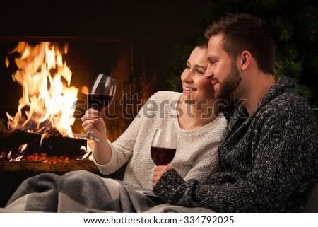 Couple relaxing with glass of wine at romantic fireplace on winter evening - stock photo