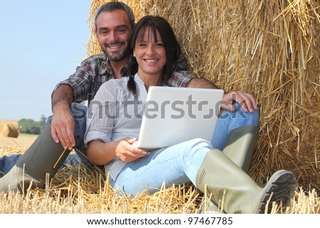 Couple relaxing with laptop in straw - stock photo