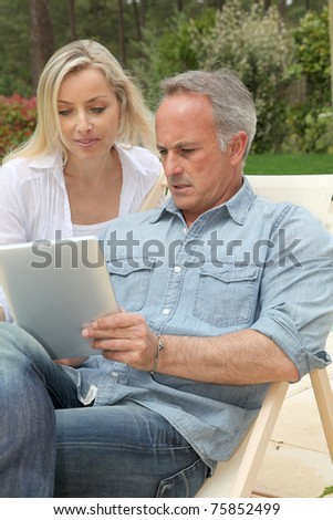 Couple resting in long chairs with electronic tablet - stock photo