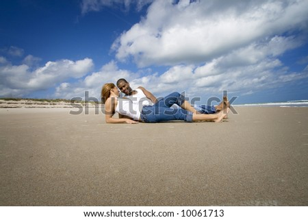 Couple resting on a beach - stock photo