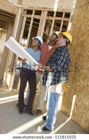Couple reviewing blueprint with builder at construction site