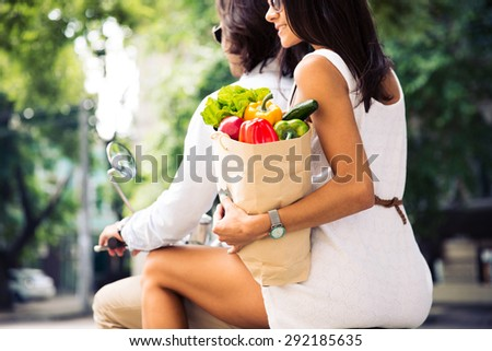 Couple riding a scooter while woman holding a shopping bag full of groceries - stock photo