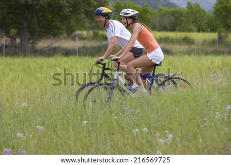 Couple riding bicycle through rural field - stock photo