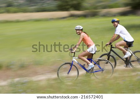 Couple riding bicycles on rural path - stock photo