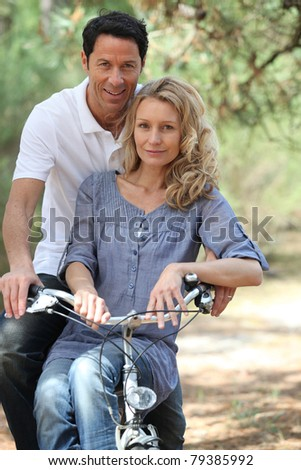 Couple riding bike in forest - stock photo