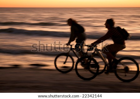 Couple riding bycicle at sunset in Honeymoon Island, Florida. - stock photo
