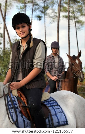 Couple riding horses together - stock photo