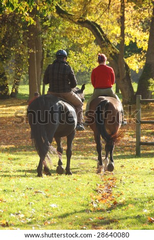 Couple riding in autumn forest - stock photo