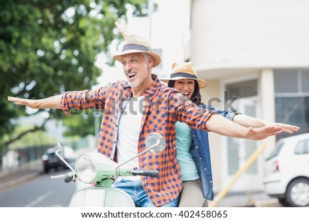 Couple riding moped with arms outstretched in city - stock photo