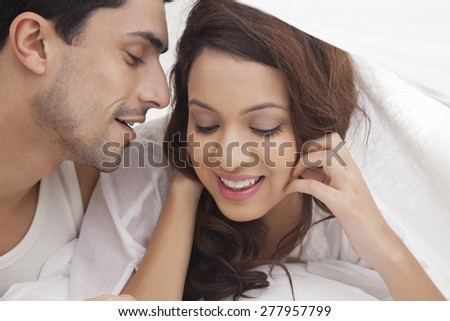 Couple romancing in bed