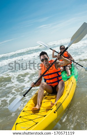 Couple rowing in kayak - stock photo