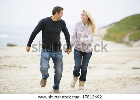 Couple running at beach holding hands smiling - stock photo