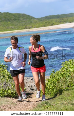 Couple running by the sea on track - stock photo