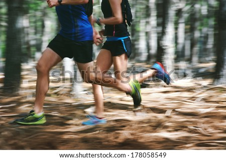 Couple running fast through the forest on trail run with motion blur - stock photo