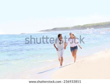 Couple running on a Caribbean beach - stock photo