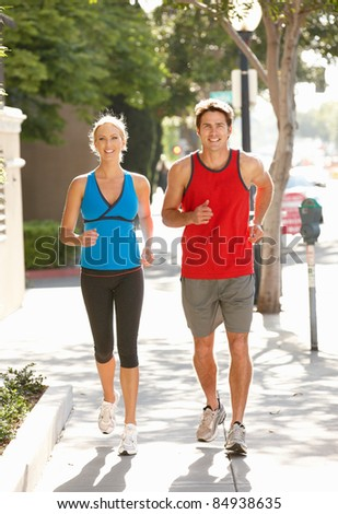 Couple running on city street