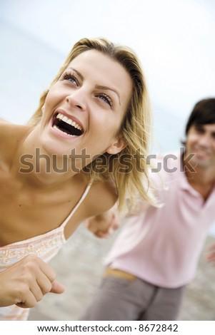 couple running on the beach - stock photo