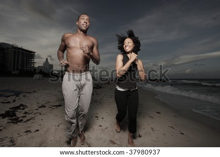 Couple running on the beach after dark